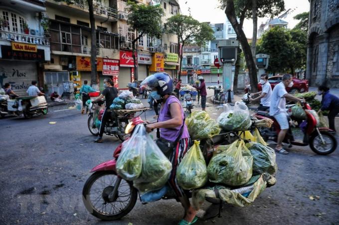 Tiểu thương và người đi chợ ngang nhiên tràn ra đường họp chợ như chưa hề có dịch bệnh, tại mặt đường Quán Thánh, khu vực bốt Hàng Đậu (ảnh chụp lúc 5h30 sáng 16/8). (Ảnh: Thành Đạt/TTXVN)