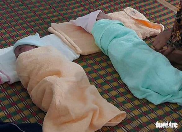 Hai bé Cô Na và Cô Vy được mọi người trợ giúp sau khi vượt cạn cùng mẹ tại nhà trước khi được đưa tới bệnh viện - Ảnh: ANH HOÀNG