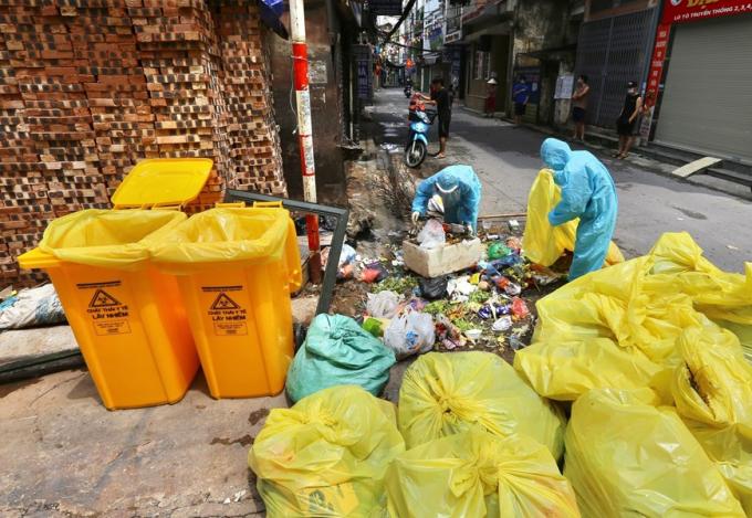 Công nhân môi trường ở các khu phong tỏa luôn làm việc trong môi trường độc hại, có nguy cơ lây nhiễm COVID-19. (Ảnh: Hoàng Hiếu/TTXVN)