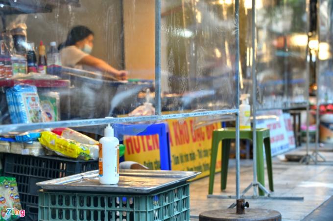 Phía dưới tấm chắn là bàn đặt thực phẩm, cùng với gel rửa tay khô. Khách hàng và tiểu thương trao đổi, mua bán qua bàn đặt, hạn chế tiếp xúc trực tiếp.
