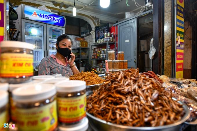 """Chị Vân (52 tuổi), chủ cửa hàng kinh doanh thực phẩm khô, gấp rút chuẩn bị các mặt hàng ngay từ tối hôm trước. """"Được thông báo cho phép mở lại khá gấp, may mắn là tôi vẫn chuẩn bị kịp số lượng hàng để bán"""", nữ tiểu thương nói."""
