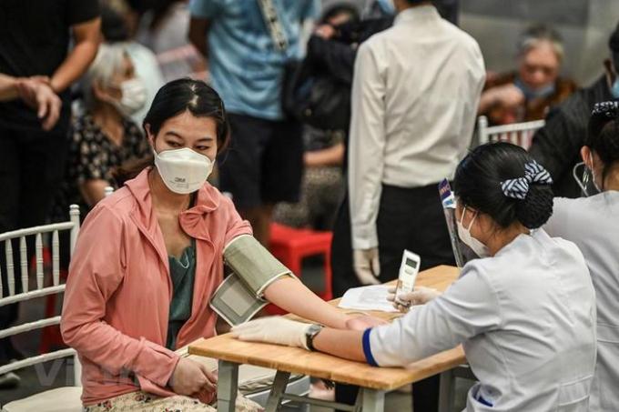 Người dân được nhân viên y tế tư vấn sức khỏe, kiểm tra huyết áp và thân nhiệt trước khi tiêm. (Ảnh: PV/Vietnam+)