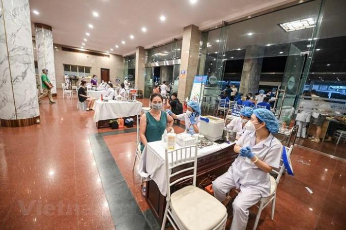 Các bàn tiêm được bố trí giãn cách đảm bảo tiêm chủng an toàn, nhanh chóng, đảm bảo. (Ảnh: PV/Vietnam+)