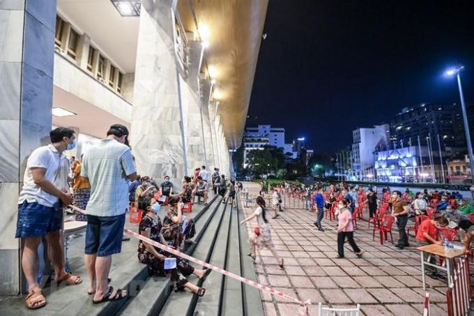 Đây là ngày đầu tiên quận tổ chức tiêm thêm vào ban đêm nhằm đáp ứng yêu cầu sớm phủ vaccine phòng COVID-19 cho người dân. (Ảnh: PV/Vietnam+)