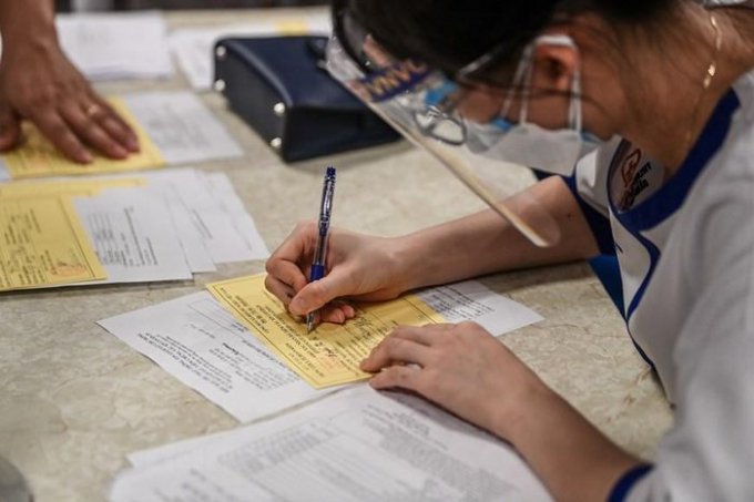 Người dân trước khi tiêm được cán bộ hướng dẫn điền các thông tin cá nhân, tiền sử bệnh nền, tình trạng sức khỏe để đảm bảo an toàn. (Ảnh: PV/Vietnam+)