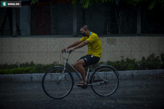 Nam thanh niên đi xe đạp dưới cơn mưa tầm tã tại ngã tư Sở sáng nay.