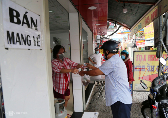 Cách đó 10 km, nhân viên quán phở ở đường Phan Văn Trị (quận Gò Vấp) liên tục yêu cầu khách xếp hàng giãn cách và phun xịt khử khuẩn khi giao nhận hàng và tiền để đảm bảo phòng dịch.
