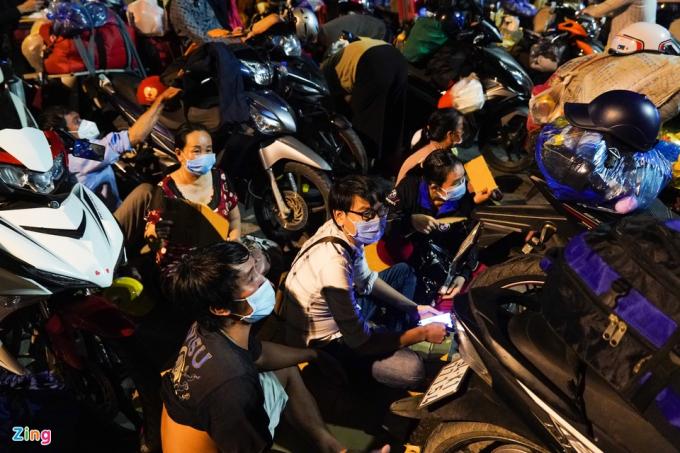 Anh Tuấn (30 tuổi) ngồi bệt xuống đất ngay trước chốt chặn. Là công nhân, anh thất nghiệp khi dịch bệnh lây lan.