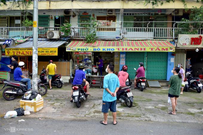 Người dân tuân thủ đứng giãn cách 1,5 m trước một tiệm phở, bò kho trên đường Sư Vạn Hạnh (quận 10) .