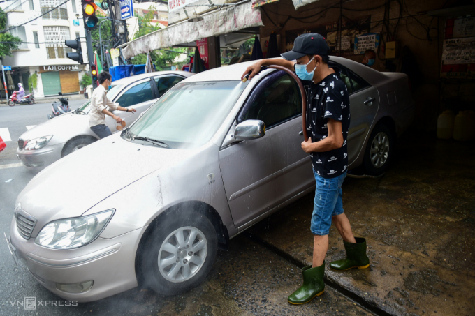 Tiệm sửa và rửa xe trên đường Nguyễn Gia Trí, quận Bình Thạnh cũng đông khách ngày mở cửa trở lại. Xe máy, ôtô xếp hàng chờ rửa, sửa sau một thời gian dài không đi lại.