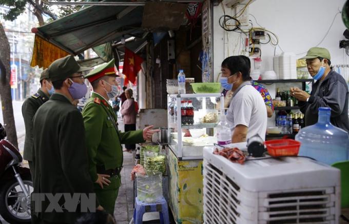 Lực lượng công an phường Hàng Mãra quân đề nghị các hộ kinh doanh đóng cửa quán ăn đường phố, trà đá, cà phê.Ảnh: Doãn Tuấn/TTXVN
