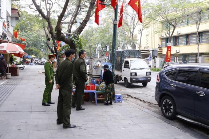 Lực lượng công an phườngCửa Namra quân đề nghị các hộ kinh doanh đóng cửa quán ăn đường phố, trà đá, cà phê.Ảnh: Doãn Tuấn/TTXVN