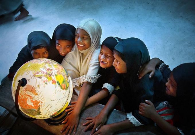 Bọn trẻ tươi cười quanh quả cầu phát sáng, tượng trưng cho sự tìm hiểu về hành tinh và môi trường. Ảnh: Pranab Basak (India)