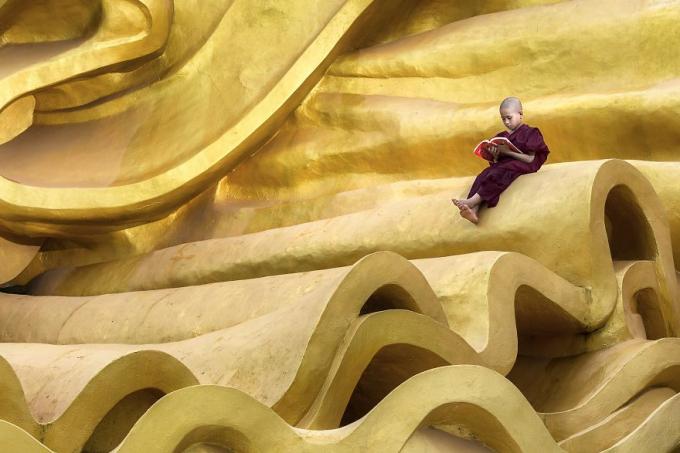 Một cậu bé đọc sách thầm lặng trên bức tượng vàng khổng lồ. Ảnh: Kyaw Myint Than (Myanmar)