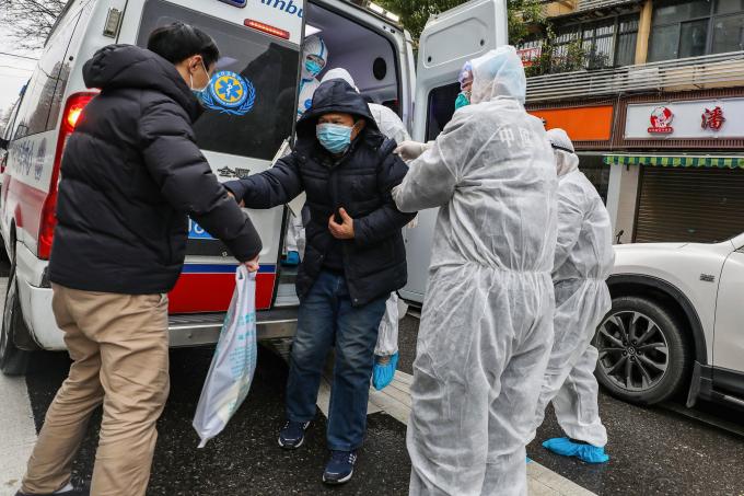 Một bệnh nhân đang được hỗ trợ bởi xe cấp cứu tại Vũ Hán(Ảnh:Agence France-Presse — Getty Images).