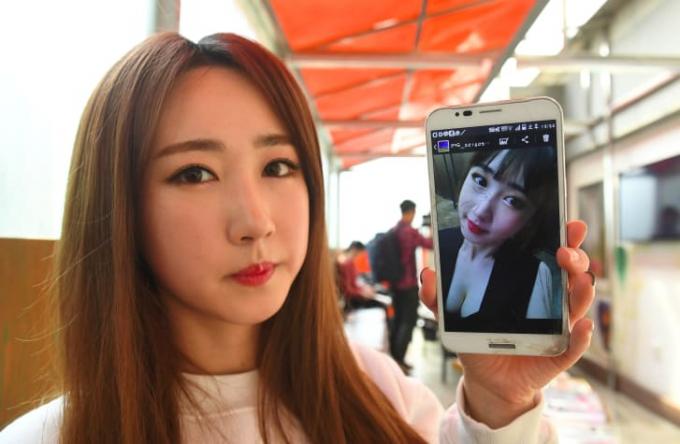 Lee So-Young, một thành viên của nhóm nhạc K-pop Sixbomb khoe tấm ảnh của cô trước khi phẫu thuật thẩm mỹ (Ảnh:JUNG YEON-JE/AFP/AFP/Getty Images).