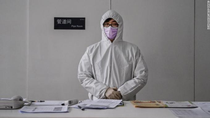 Một nhân viên đeo trang phục bảo hộ đứng trước sảnh đợi quét thân nhiệt những ai bước vào tòa nhà văn phòng ở Bắc Kinh hôm 10/2.