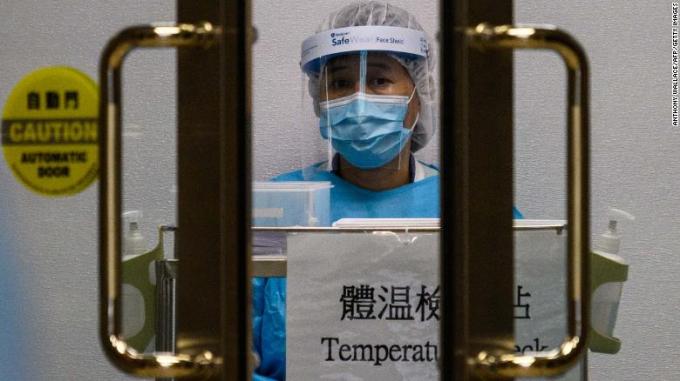 Một nhân viên y tế mặc trang phục bảo hộ đứng đợi để kiểm tra thân nhiệt những người bước vào bệnh viện Princess Margaret tại Hong Kong hôm 4/2.