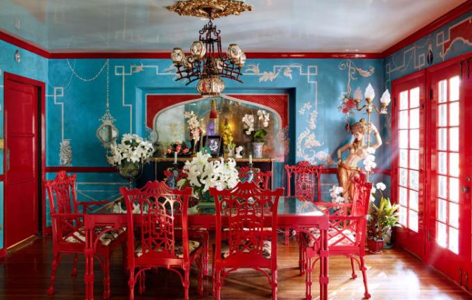Phòng ăn màu đỏ nổi bật trên nền tường màu xanh.