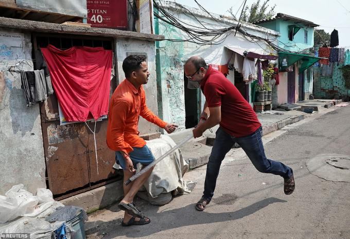 Cảnh sát mặcthường phụcđang đánh vào chân một người khi anh này tự ý ra ngoài trong lệnh phong tỏa 21 ngày ở Kolkata