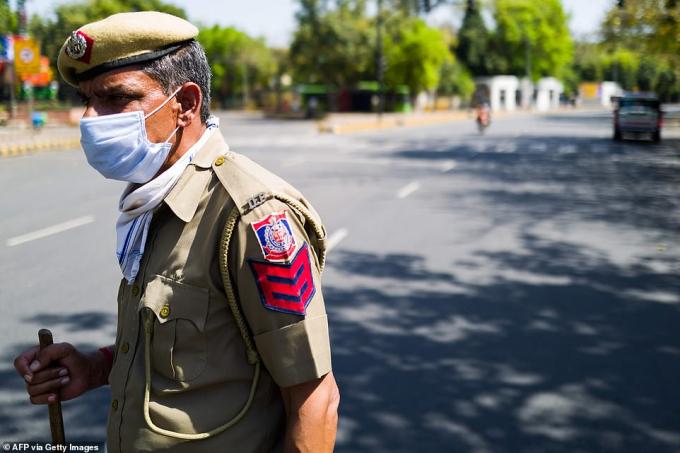 Một cảnh sát đứng canh một đoạn đường bị chặn trong ngày đầu tiên của chiến dịch 21 ngày phong tỏa của nước này