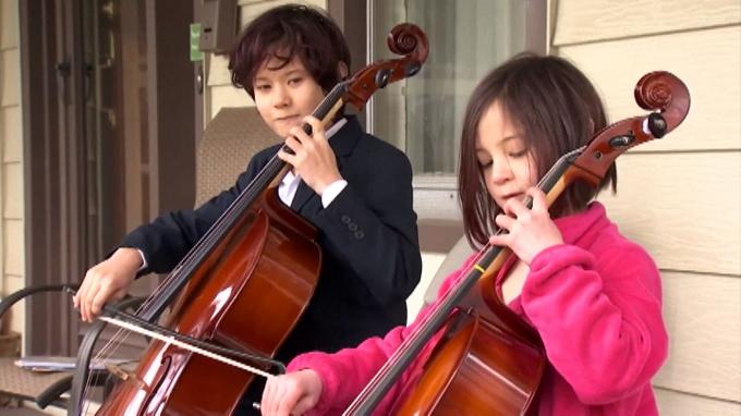 Hình ảnh cậu bé Taran Tien cùng em gái biểu diễn nhạc bên ngoài nhà của một hàng xóm đang phải cách ly vì Covid-19 tại Ohio, Mỹ.