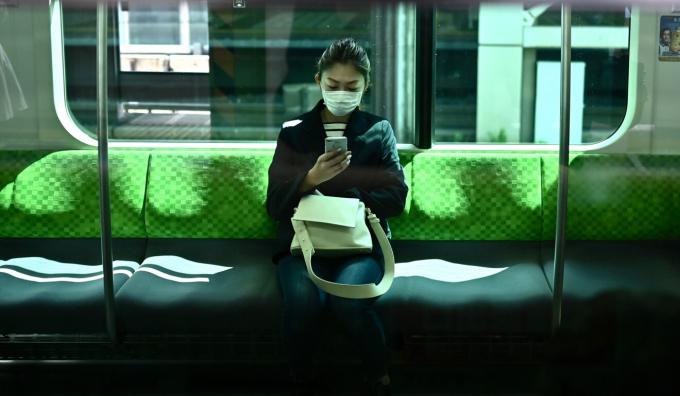 Một phụ nữ dùng điện thoại trên một chuyến tàu vắng khách ở Tokyo vào ngày đầu tiên của tình trạng khẩn cấp (Ảnh AFP)