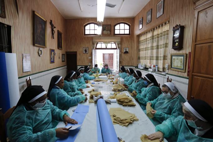 Các nữ tu Agustinian của tu viện San Leandro thay vì làm món bánh truyền thống của tu viện đã chuyển sang làm khẩu trang và áo choàng y tế (Ảnh: Marcelo del Pozo   Getty Images).