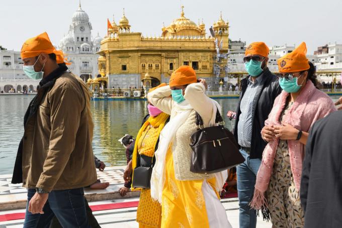 Các tín đồ đeo khẩu trang do lo ngại dịch bệnh lan truyền, đến cầu nguyện tại đền thờ vàng Golden Temple ở Amritsar (Ảnh: Narinder Nanu   AFP   Getty Images)