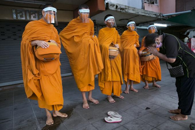 Các tu sĩ Phật giáo đeo kính chống giọt bắn trước e ngại lan truyền dịch Covid-19 khi nhận bố thí từ người dân trên đường phố Bangkok (Ảnh: Allison Joyce/ Getty Images).