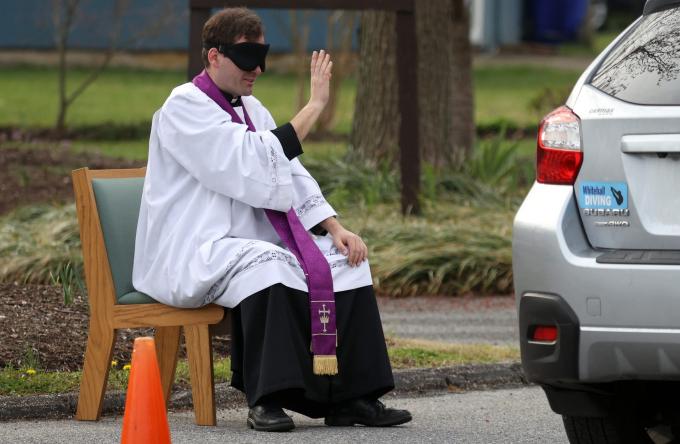 Mục sư Scott Holmer của Nhà thờ Công giáo St. Edward làm dấu thánh giá khi đang tiếp nhận lời xưng tội trong một khu vực để xe của nhà thờ (Ảnh: Rob Carr/ Getty Images).