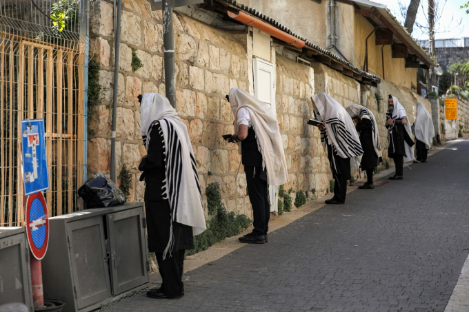 Những tín đồ Do Thái đeo chiếc khăn Tallit truyền thống cầu nguyện dọc theo một con phố bên ngoài giáo đường kín của họ tại Jerusalem hôm 29/3, trong khi vẫn giữ khoảng cách 2 mét như yêu cầu nhằm ngăn ngừa sự lây lan dịch bệnh (Ảnh: Menahem Kahana   AFP   Getty Images).