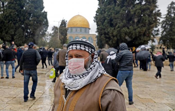 Một người đàn ông Palestine đeo khẩu trang bảo hộ, đứng trước đền thờ Mái vòm Dome of Rock bên trong nhà thờ Hồi giáo Al-Aqsa tại thành phố cổ Jerusalem (Ảnh: Ahmad Gharabli/AFP/Getty Images).