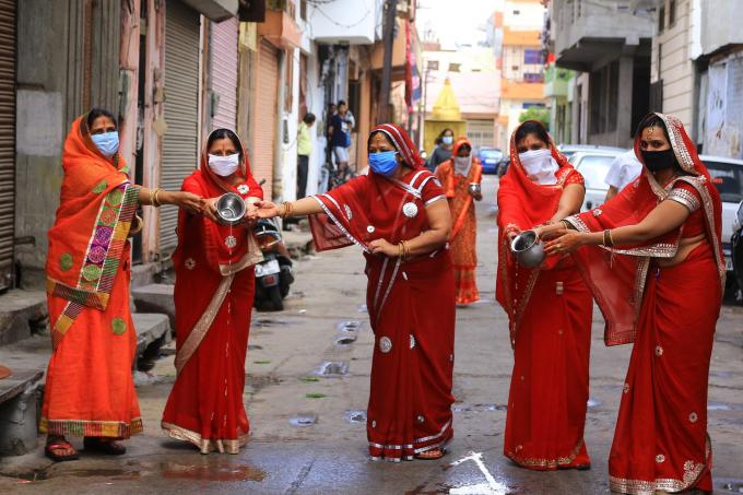 Những phụ nữ đạo Hindu dâng nước cho thần mặt trời trong lúc thực hiện nghi thức của lễ hội Gangaur khi lệnh phong tỏa tại quốc gia này bị áp đặt (Ảnh: Vishal Bhatnagar   NurPhoto   Getty Images).