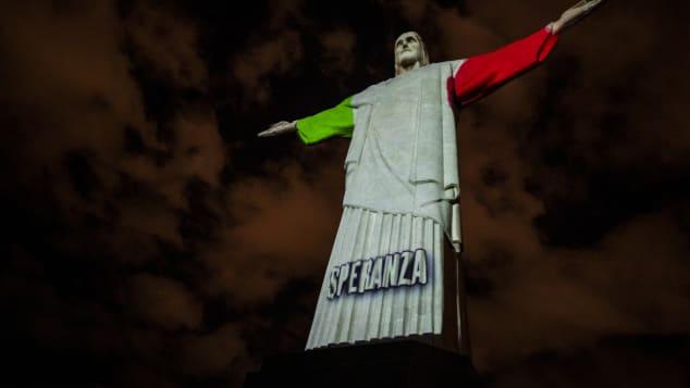 Hình ảnh quốc kỳ của Italy cùng thông điệp bằng tiếng Ý được chiếu trên bức tượng (Ảnh:Buda Mendes/Getty Images).