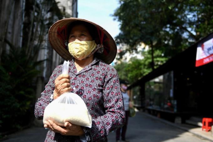 Một phụ nữ đeo khẩu trang nhận túi gạo miễn phí tại một góc phố cổ Hà Nội hôm 27/4/2020 (Ảnh: AFP/ Nhac Nguyen).