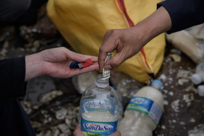 Các nhà hoạt động đổ đầy chai nhựa bằng gạo, tiền và một thẻ USB chứa K-Pop để ném xuống biển về phía Triều Tiên trên đảo Ganghwa, Hàn Quốc năm 2018 (Ảnh:Ed Jones/AFP/Getty Images).