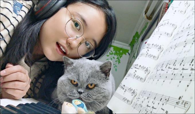 Cô giáo dạy piano Mary Zhu bên một trong hai chú mèo của mình