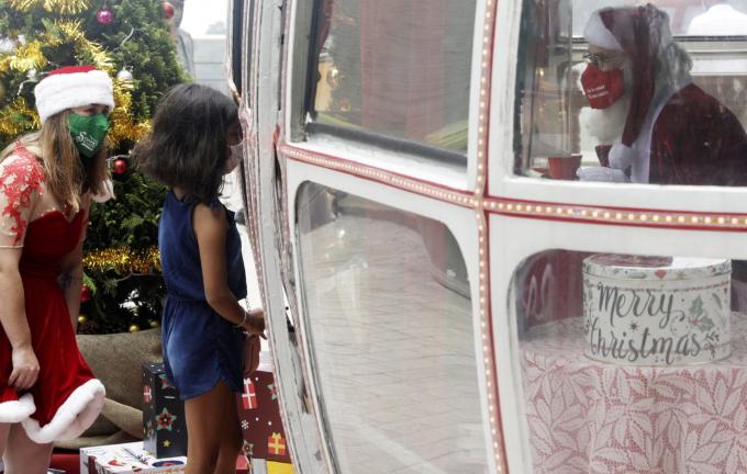 Một bé gái ghé thăm ông già Noel trong một khoang cáp treo cũ gần dãy núi Sugar Loaf tại Rio de Janeiro, Brazil (Ảnh: Ricardo Moraes/Reuters).