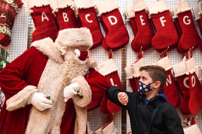 Ông già noel Santa Claus thực hiện động tác chào hỏi bằng khuỷu tay với cậu bé Jaythan Corbacho tại một cửa hàng ở London, Anh (Ảnh: Eamonn M McCormack/Getty Images).