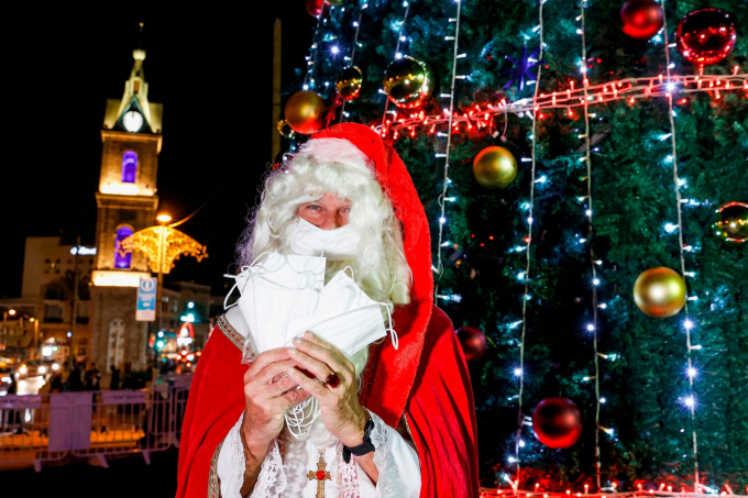 Một người đàn ông khoác trang phục Santa Claus trao những chiếc khẩu trang cho người qua đường tại Tel Aviv, Israel (Ảnh: Jack Guez/AFP/Getty Images).