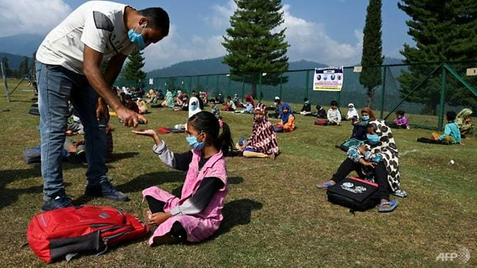 Trước buổi học, các em phải đeo khẩu trang và thầy giáo sẽ giúp vệ sinh và diệt khuẩn cho từng em một (Ảnh: AFP)