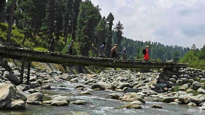 ...Và phải qua cả những cây cầu dài bắc qua suối để tới trường (Ảnh: AFP)